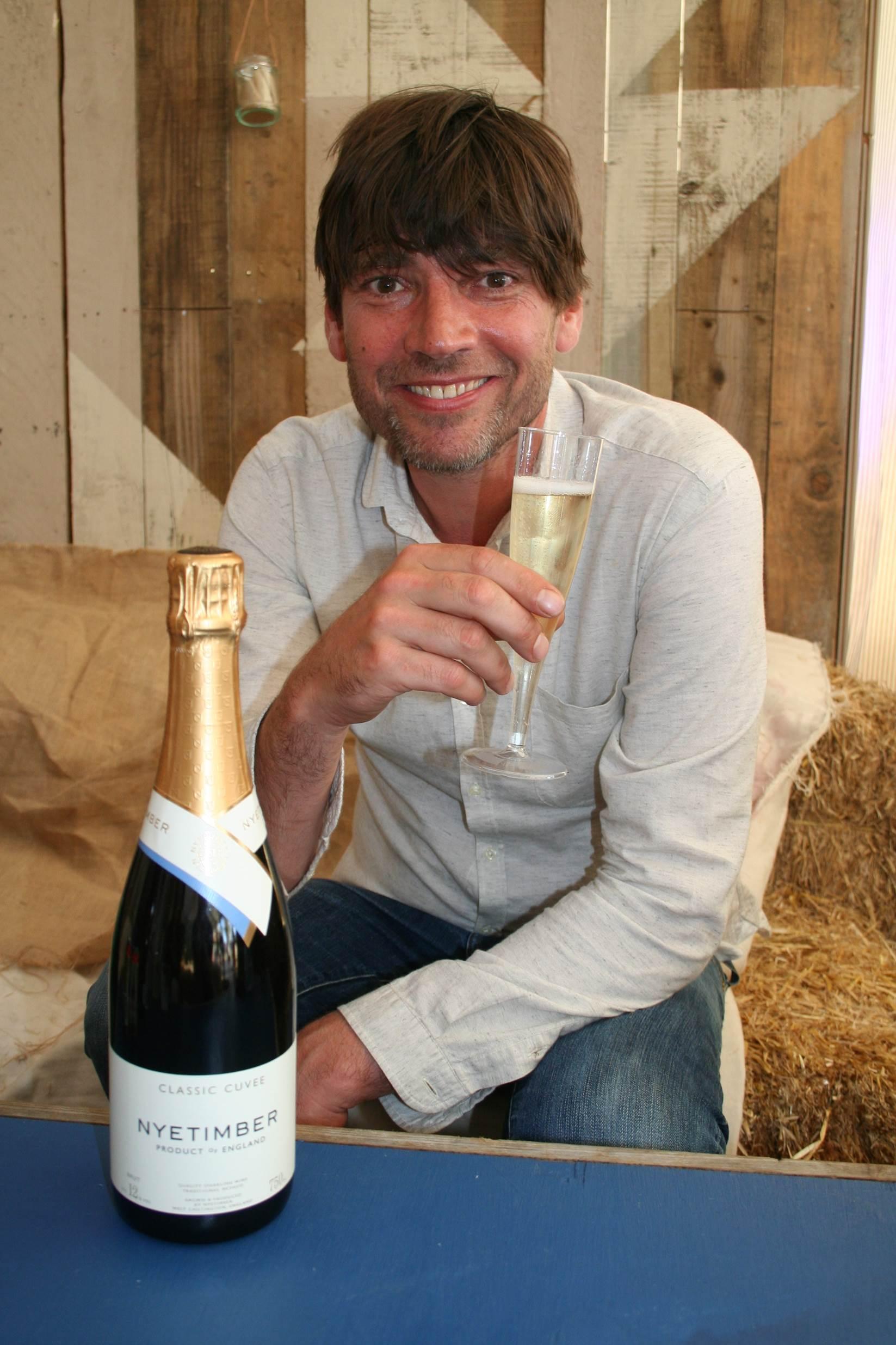 a man sat behind a bottle of wine enjoying a glass