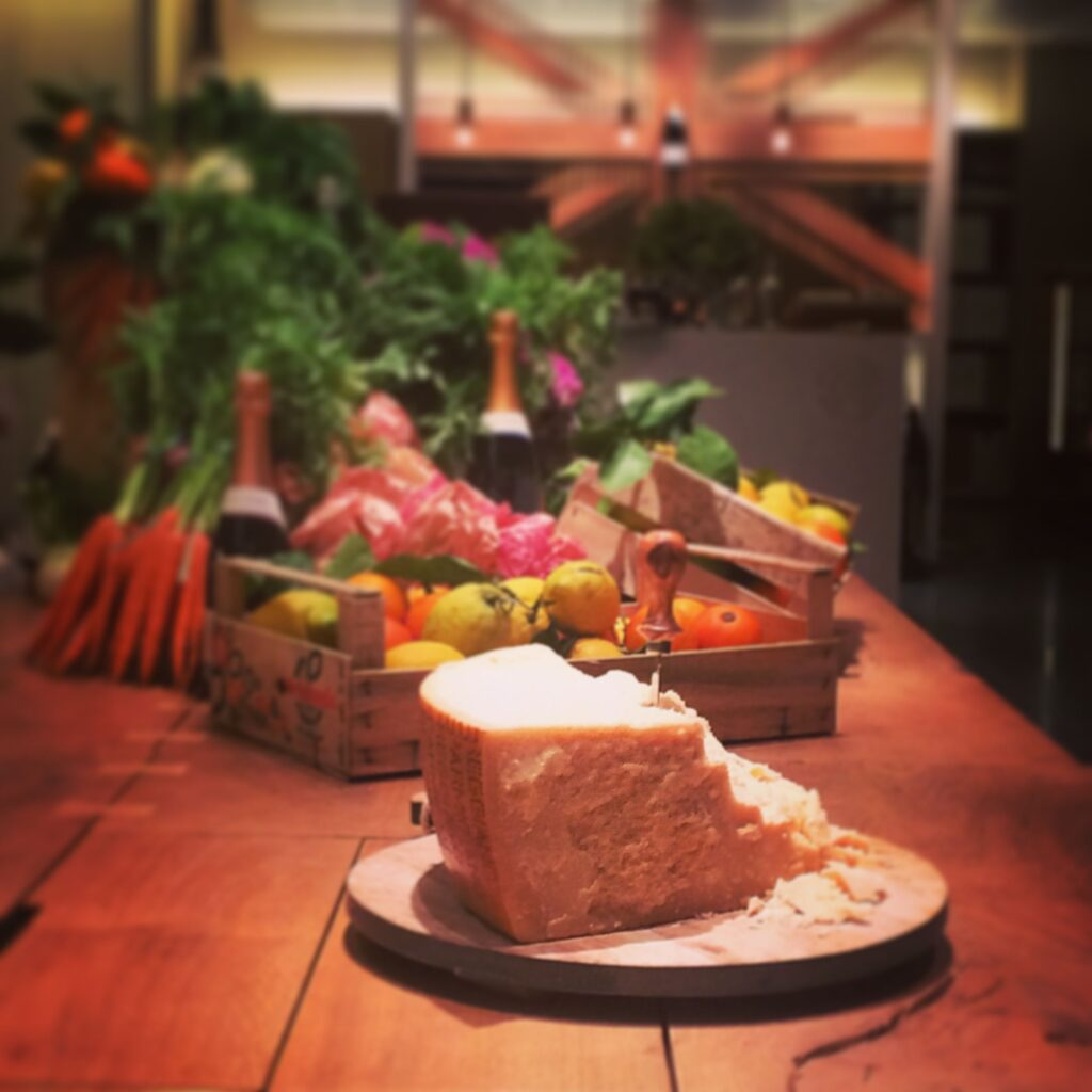 a block of cheese in front of carrots, lemons, pink and purple flowers and bottles of wine
