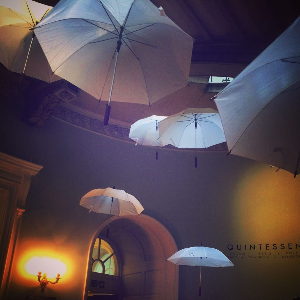 seven umbrellas in a room suspended in the air at different heights