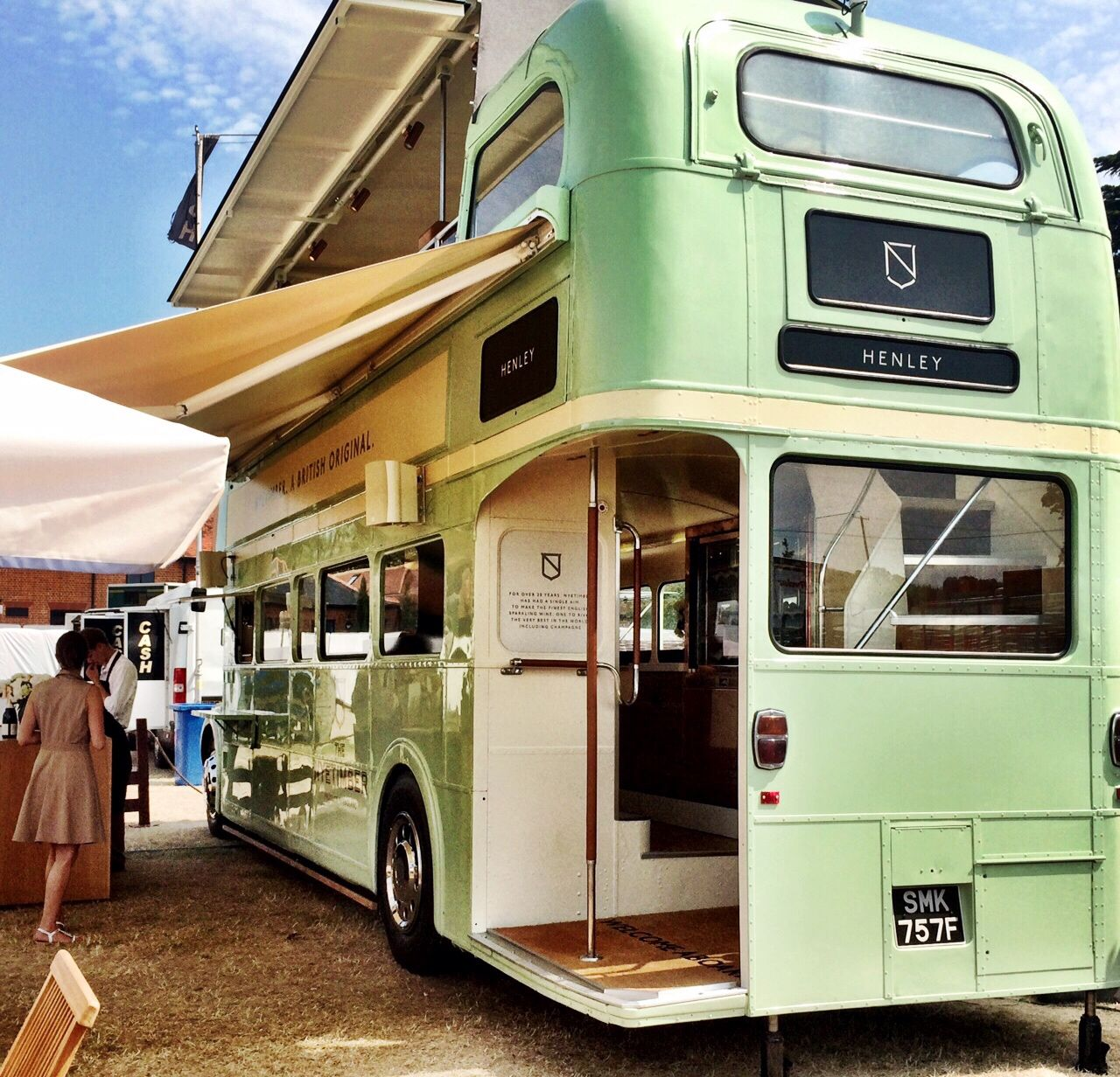 the back of a green vintage open top bus, with a pull out awning