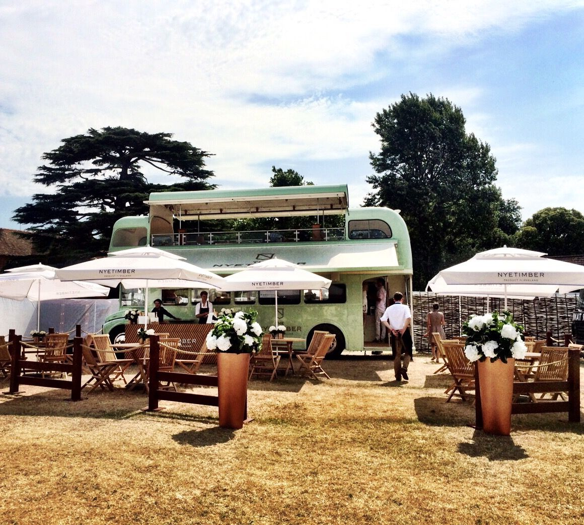 a green vintage open top bus, set out for dining with chairs, tables and parasols, decorated with white flowers