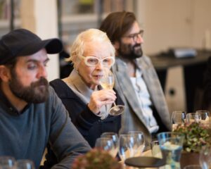 vivienne westwood sat between two men drinking wine