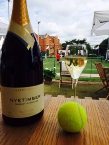 a bottle and glass of wine with a tennis ball, overlooking a tennis match