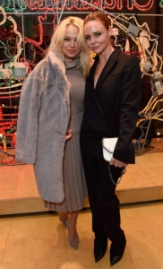 pamela anderson and stella mccartney pictured in front of christmas decorations