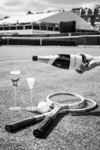 pouring wine into glasses on a tennis court