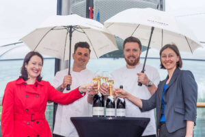 four people toasting wine glasses, holding umbrellas while at a sky bar