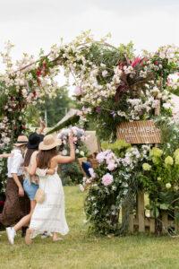 women going under floral arch