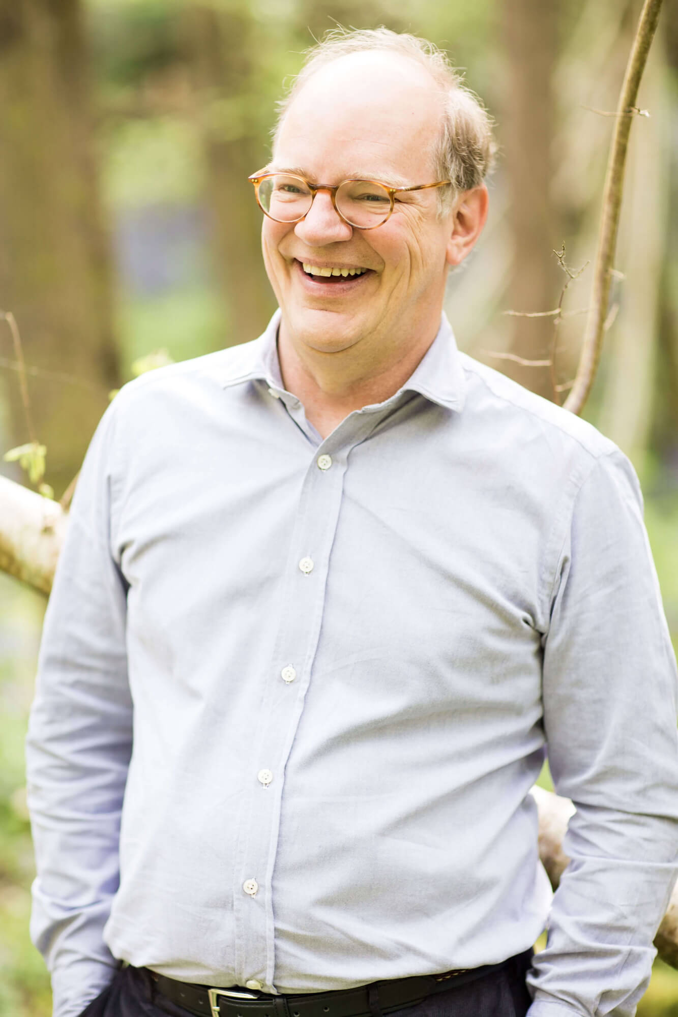 a man with glasses, hands in his pockets, smiling