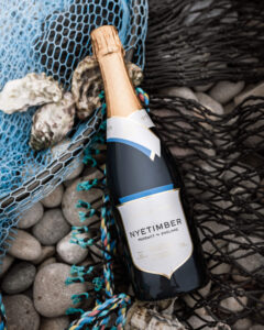 wine bottle laid on fishing net and pebbles