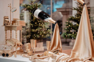 suspended wine bottles with gold silk flowing from the opening