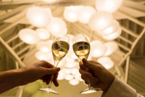 two wine glasses toasting under lights